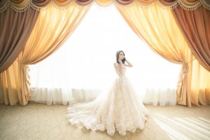 woman wearing white gown near window curtain