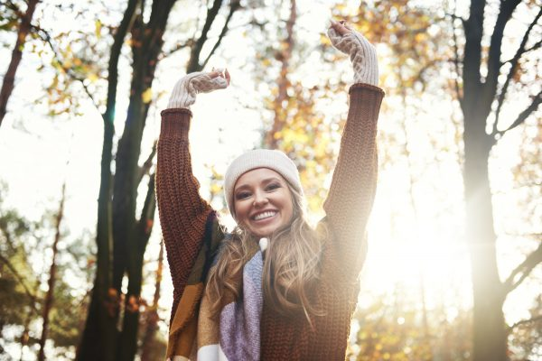 Portrait of beautiful woman with hands raised in autumn forest