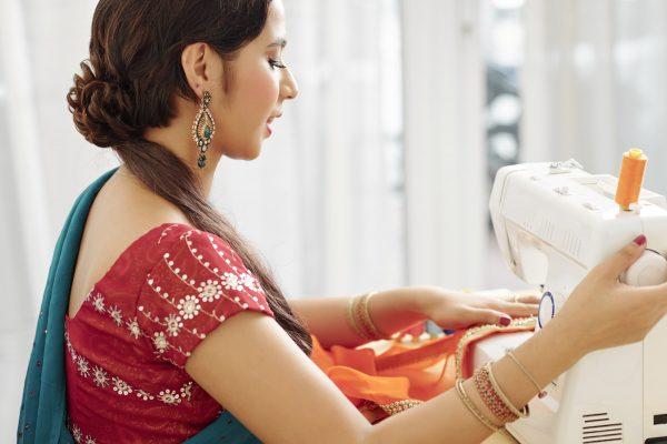 Woman sewing silk sari dress