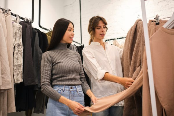 Young designer showing clothes from new collection to attractive Asian girl in clothes store