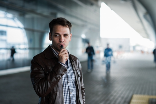 Urban lifestyle portrait of a man vaping near the airport before registration with custom vape mod